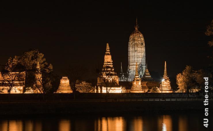 Bild Wat Phutthaisawan bei Nacht - Ayutthaya zeigt den erleuchteten Tempel mit Spiegelung im Fluss.