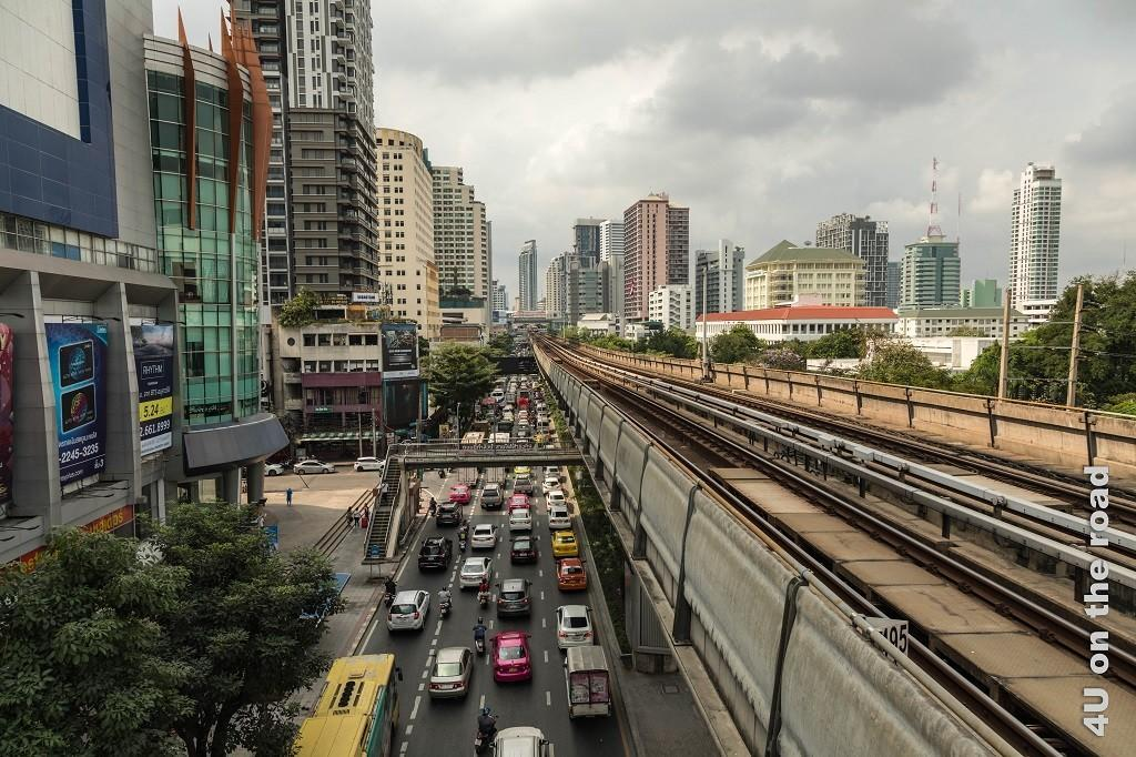 Bild Aussicht von der Plattform des Skytrains in Bangkok, Stau auf der vierspurigen Strasse, gerahmt von Hochhäusern und den leeren Skytrainschienen