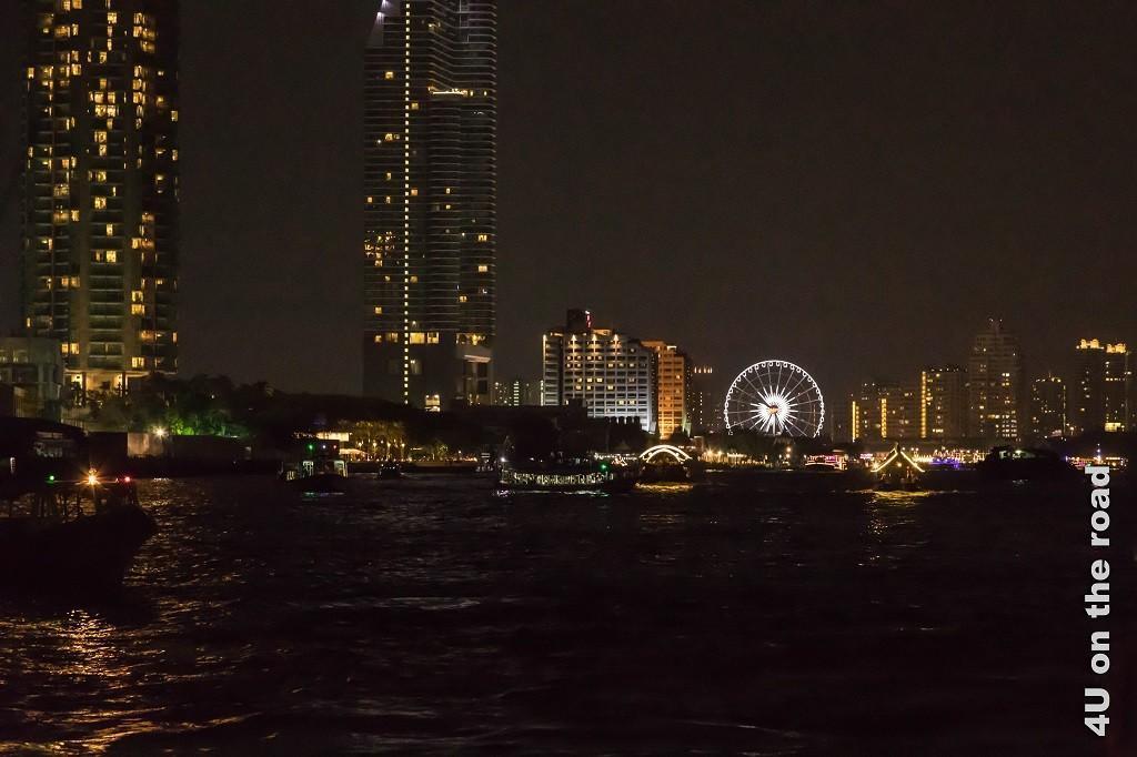 Bild Blick zurück Bangkok bei Nacht, das Bild zeigt beleuchtete Hochhäuser und ein Riesenrad