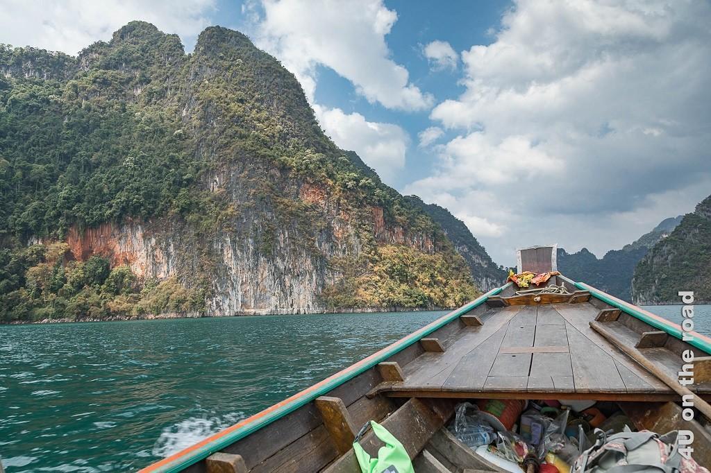 Bild Cheow Lan Lake – Bootstransfer zum Flosshaus, neben der Longbootspitze sind bunte, bewachsene Kalksteinfelsen am Uferrand zu sehen
