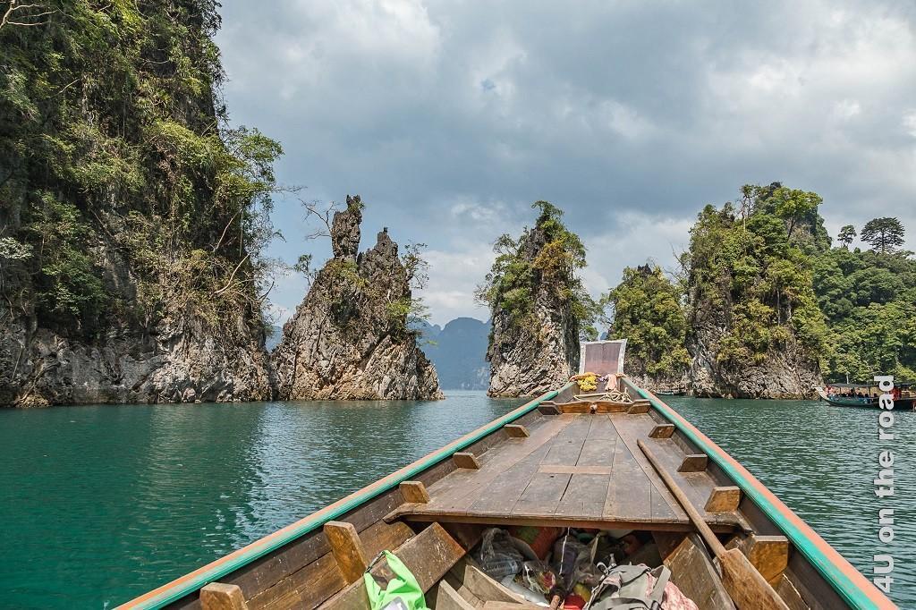 Bild Cheow Lan Lake - die drei berühmten Felsen, die Longbootspitze zeigt auf 3 schlanke mitten im Wasser stehende bewachsene Kalksteinfelsen