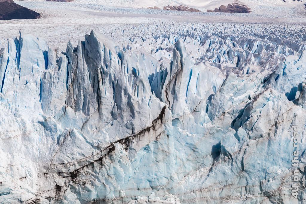 Bild Die Farben des Gletschers, spitze Gletscherzacken schimmern von weiss bis blau von schwarzen Linien durchzogen