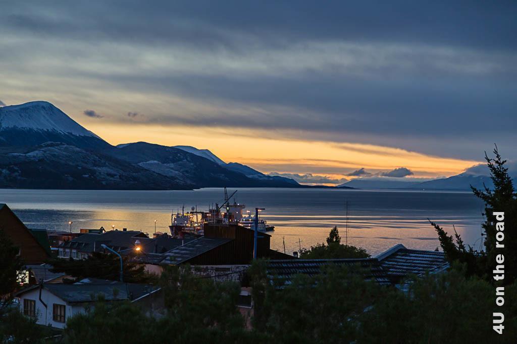 Bild Kurz bevor die Sonne in Ushuaia aufgeht, zeigt zur blauen Stunde das erste orange Licht am Horizont mit Spiegelung im Wasser.