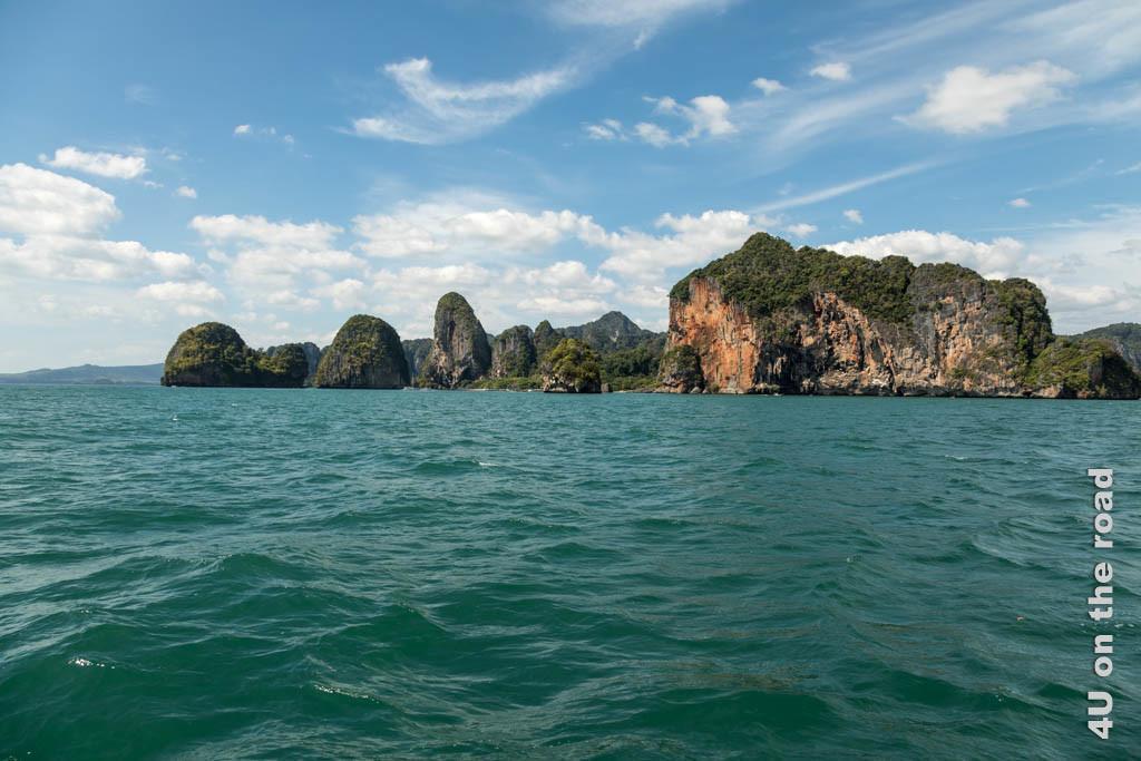 Bild Land in Sicht, türkisfarbenes Wasser und bunte Kalksteinfelsen gerahmt von blauem Himmel mit wenigen weissen Wölkchen