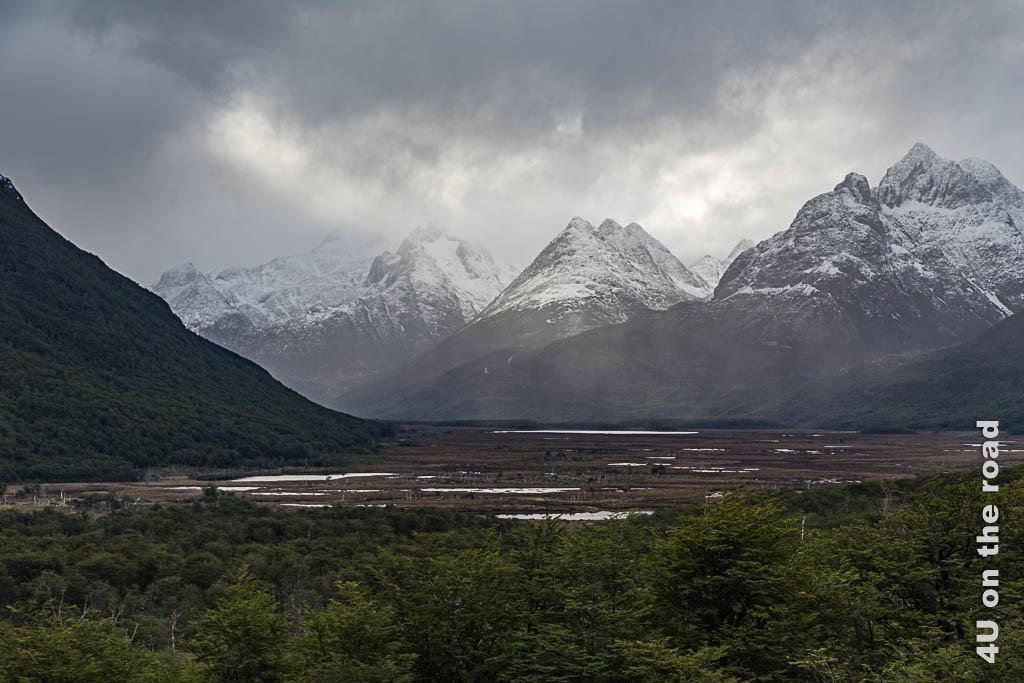 Bild Lichtstimmung auf dem Weg zum Biber, schneebedeckte Bergspitzen, Nebel und Wolken im Hintergrund, im Vordergrund Moor