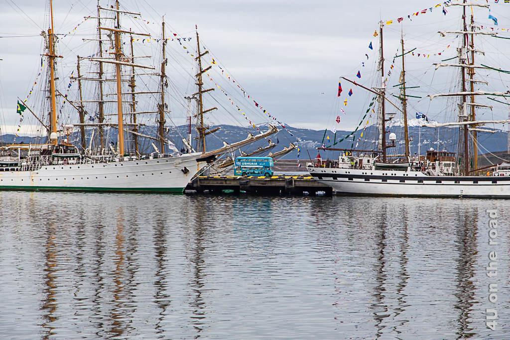 Bild zwei Segelschiffe rahmen einen blauen Doppelstockbus im Hafen von Ushuaia