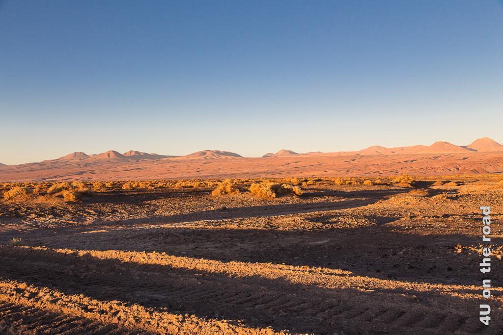 Bild Abendsonne in der Atacama. Die Felsen und hügel leuchten orange.