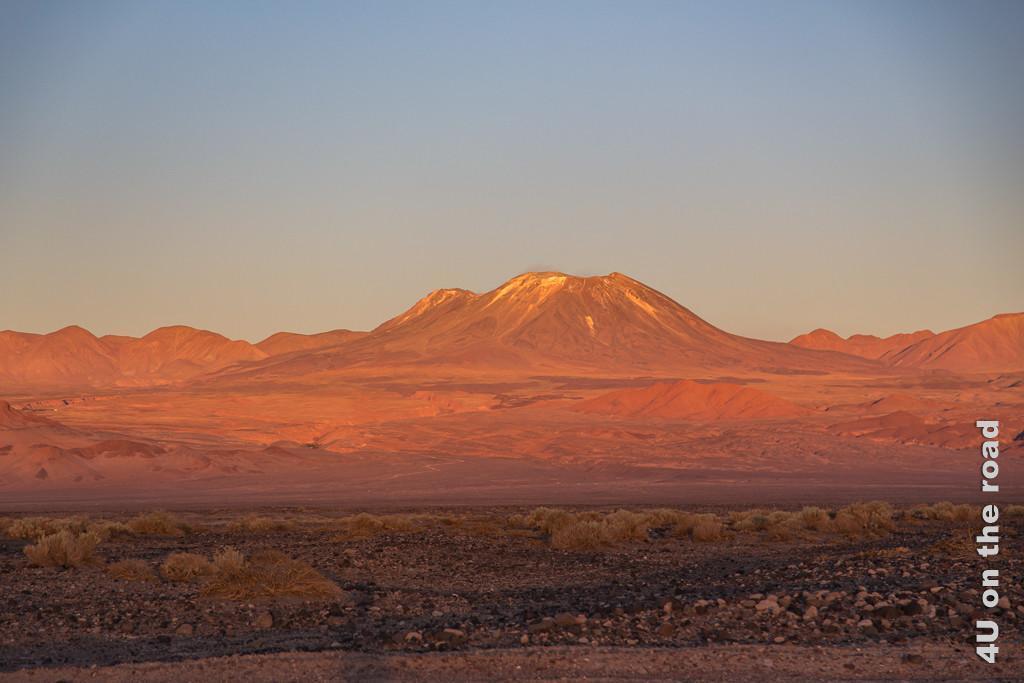 Bild Kurz bevor die Sonne hinter dem Horizont verschwindet, Atacama, taucht sie den Vulkan und die Hügel in leuchtendes Orange.