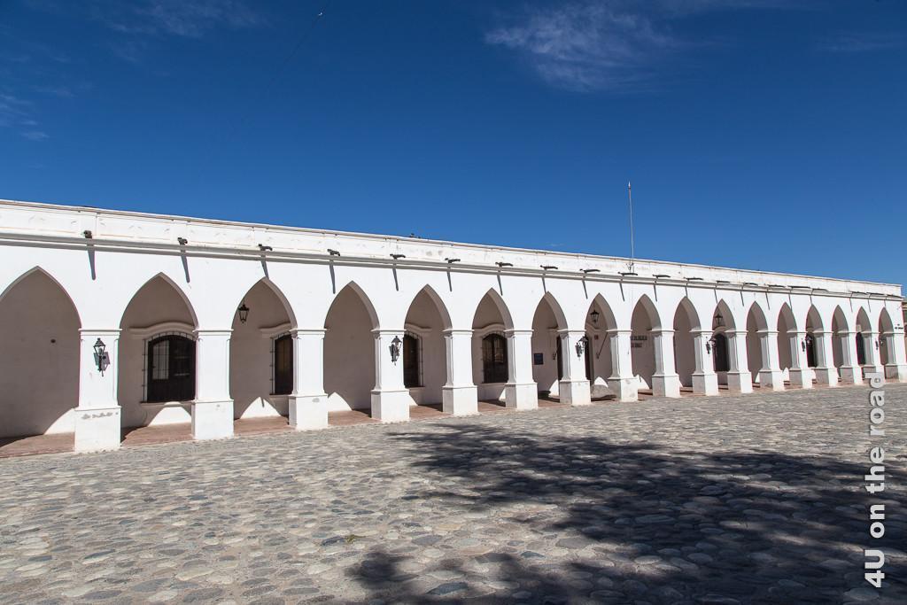 Bild Front des Archäologischen Museums in Cachi. Das Gebäude ist einstöckig, weiss getüncht, vor der gesamten Front erstreckt sich ein tiefer Arkadengang mit spitz zulaufenden Bogendurchbrüchen. Der Vorplatz ist gepflastert.