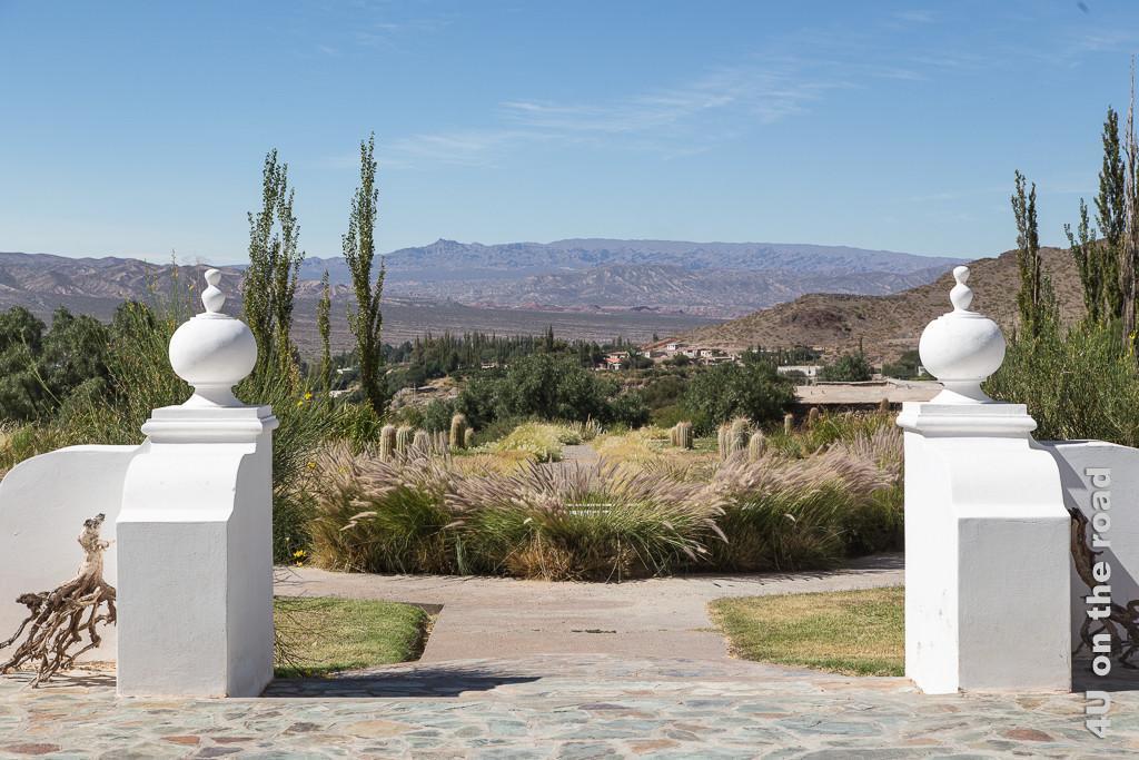 Bild Ausblick von der Terrasse des Klosters La Merced del Alto auf Cachi, zwischen zwei weissen Steinpfosten hindurch blickt man entlang eines von Kakteen gesäumten Weges über Bäume auf das tiefer liegende Cachi, die Talebene und Berge hinter der kleinen Stadt.