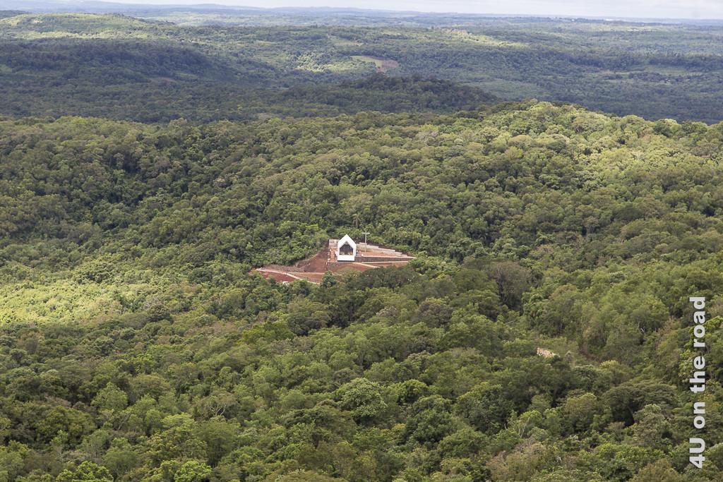 Bild Parque de la Cruz - Blick vom Kreuz herab auf die moderne Kirche. Eingebettet in den bis in den Bildhintergrund reichenden, dichten Urwald, ist im Vordergrund ein modernes Kirchengebäude, von dem nur das rote, ziegelgedeckte Dach, der Glockenaufbau und das Kreuz zu sehen sind.