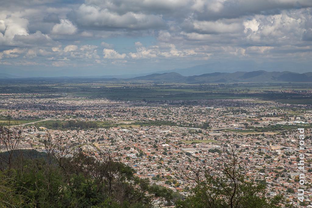 Bild Blick vom San Bernardo in die Ferne. Ein Meer aus Häusern ergiesst sich in einem breiten Tal unterbrochen von grünen Flächen.
