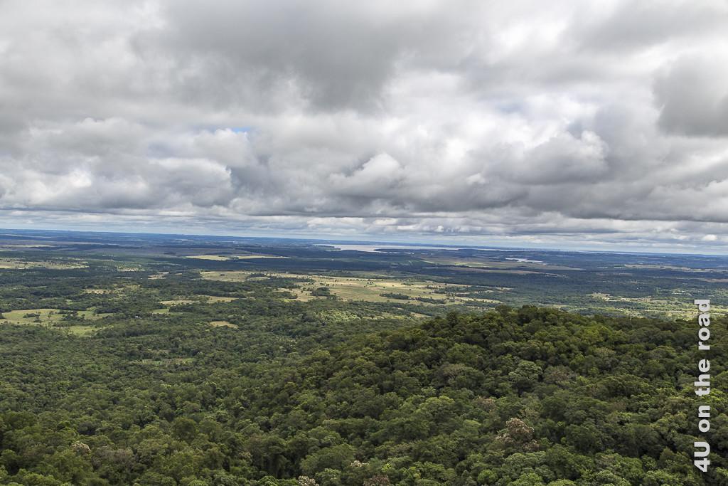 Bild Blick von oben vom Kreuz im parque de la Cruz auf den Rio Parana. Weite Waldflächen in der Bildmitte von ein paar Feldern unterbrochen. In der Ferne eine Flussbiegung. Darüber eine niedrige und dichte Decke aus einzelnen Wolken.