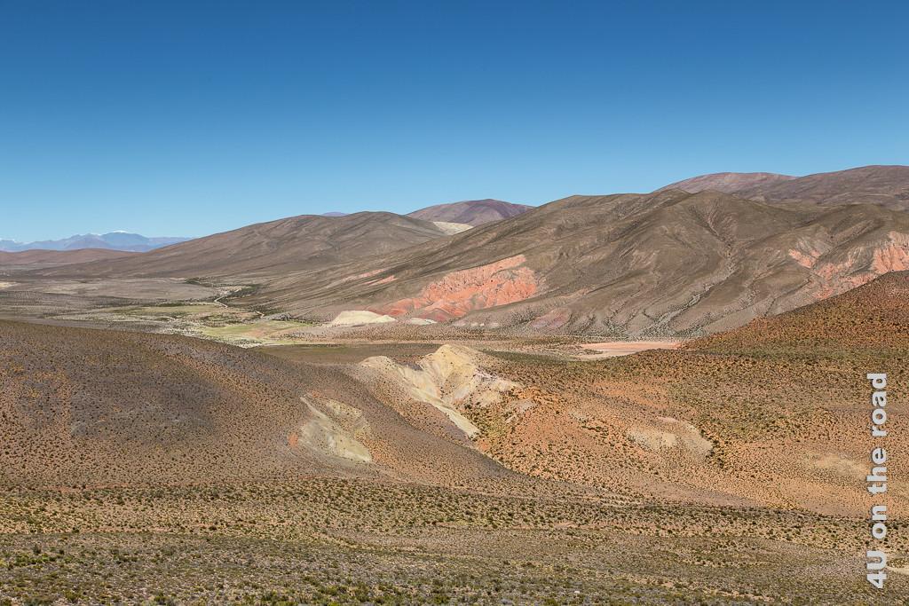 Bild Blick zurück in die Hochebene, rötliche Felsen, schneebedeckte Vulkane und Grün am Fusse der Berghänge