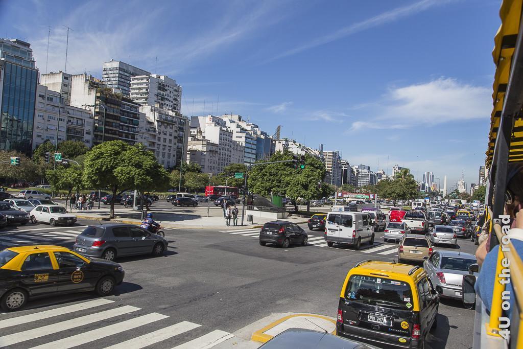 Bild Buenos Aires - Avenida 9 de Julio. Eine extrem breite Avenida mit mindestens 2 Spurgruppen je Richtung, insgesamt ca. 16 bis 20 Fahrspuren. Dazwischen Baumreihen und das ganze gesäumt von im Mittel 10-stöckigen Wohn und Bürohäusern.