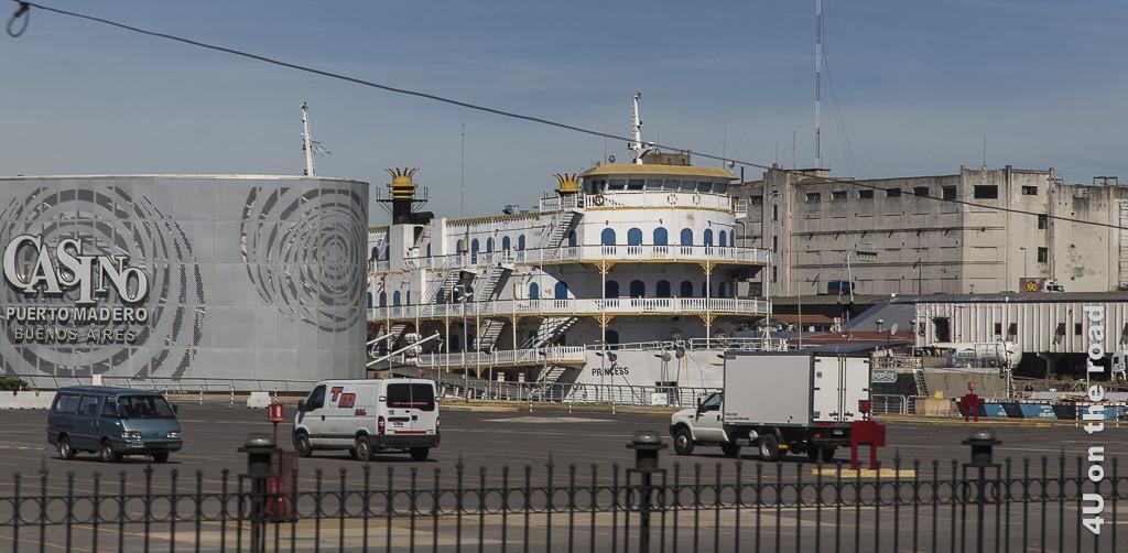 Bild Buenos Aires - Casino. Neben der grauen, modernen Casinofront ist ein 3-stöckiges Dampfschiff nach Art der Mississippi-Dampfer vertäut. Es liegt am Hafen Puerto Madero.