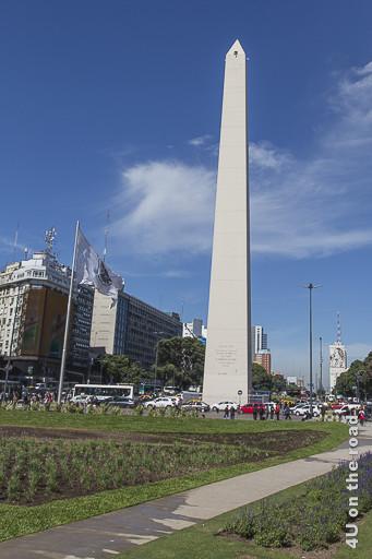 Buenos Aires - Der Obelisk auf der Avenida 9 de Julio. Er ist mindestens 50 Meter hoch und steht auf einem begrünten Platz zwischen den Fahrspuren.