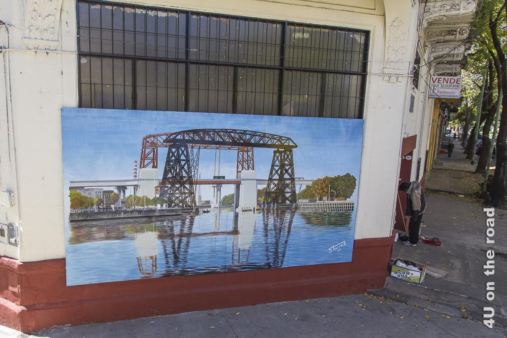 Bild Buenos Aires - La Boca. Vor einem grossen in einer Hauswand präsentiert ein lokaler Künstler ein Grossgemälde, circa 3 mal 1.5 Meter, welches eine grosse moderne Zugbrücke über einen Kanal darstellt.