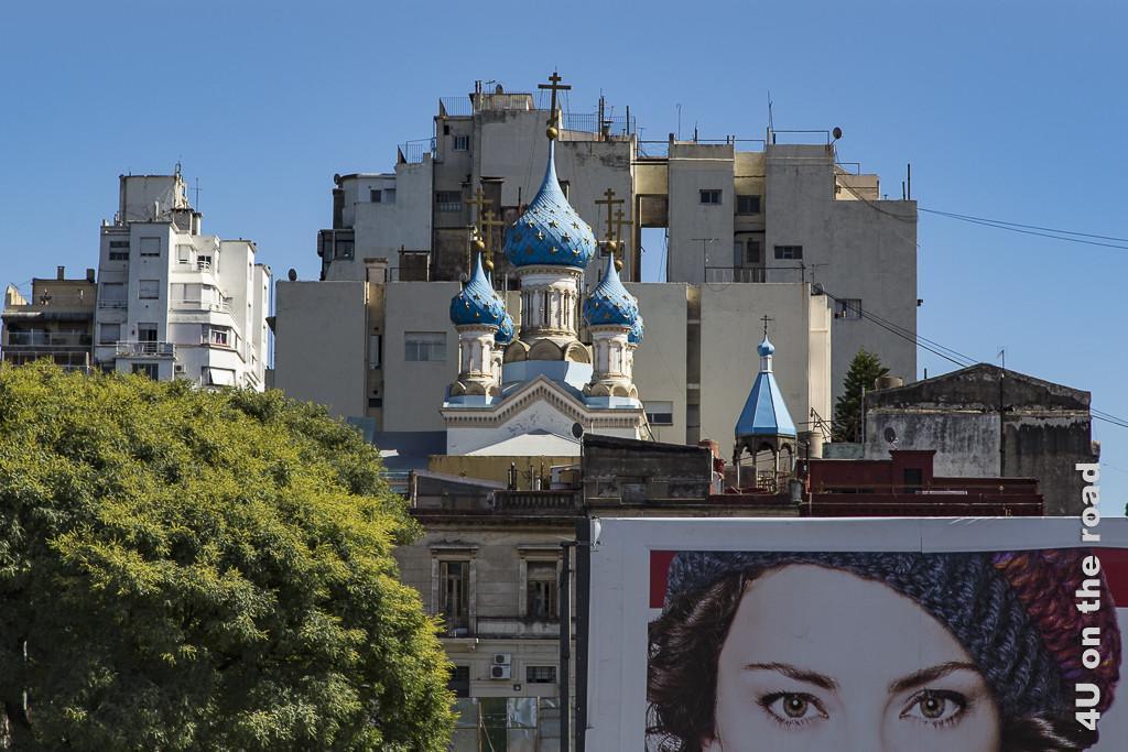 Bild Buenos Aires - Stilmix. Im Vordergrund eine Plakatwand. Dahinter etwas schäbige 2 bis 3-stöckige Wohnhäuser. Dahinter eine Zwiebelturmkirche mit blauen Turmdächern, dahinter wiederum ein die Kirche überragender sehr hässlicher Wohnblock.