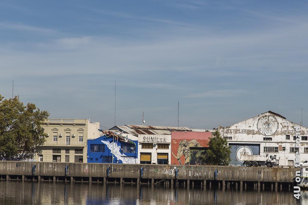 Bild Buenos Aires - alte Fabriken. Es zeigt alte, niedrige Fabrikgebäude und -hallen mit abblätterndem Putz am einbetonierten Ufer eines Flussarms.