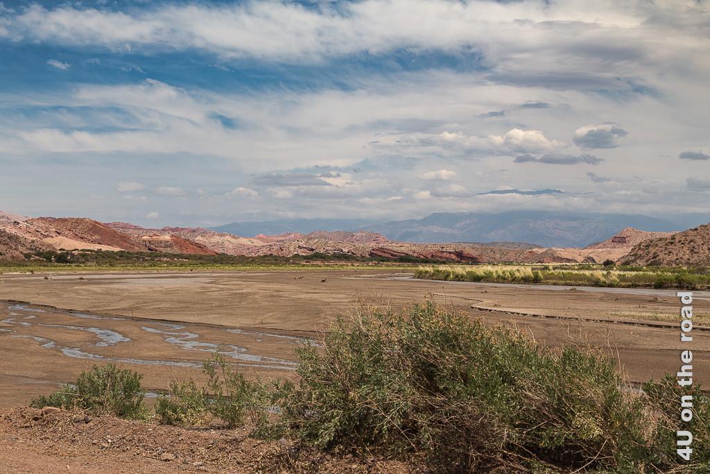 Bild Der Fluss hat wohl manchmal auch deutlich mehr Wasser. Ein sehr breites, flaches Flussbett zeigt nur am Rand ein kleines Rinnsal. Umliegende rote Felshügel und im Hintergund eine höhere Bergkette.