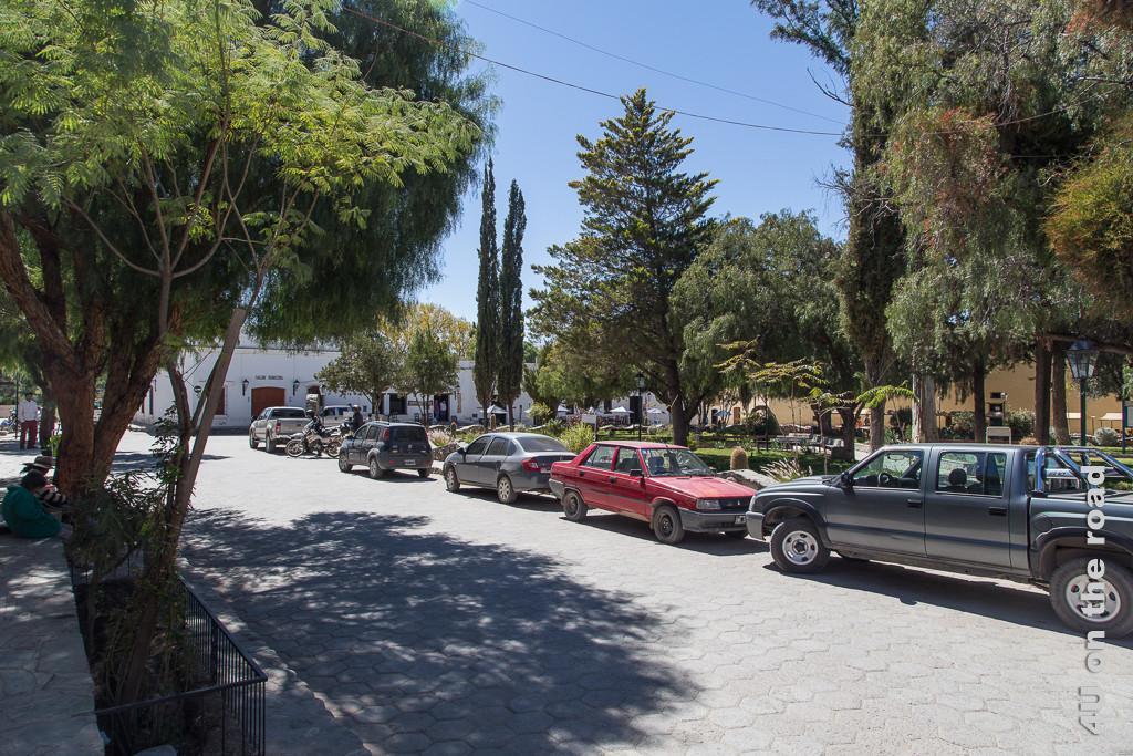 Bild mit Blick auf den für südamerikanische Städte typischen kleinen, zentralen Park von Cachi, umrundet von gepflasterten Strassen. Hier mit einigen geparkten Autos, teils staubbedeckt. Hinter dem Park scheinen weiss getünchte ein- bis zweigeschossige Gebäude durch, die die Strassen auf der Aussenseite säumen.