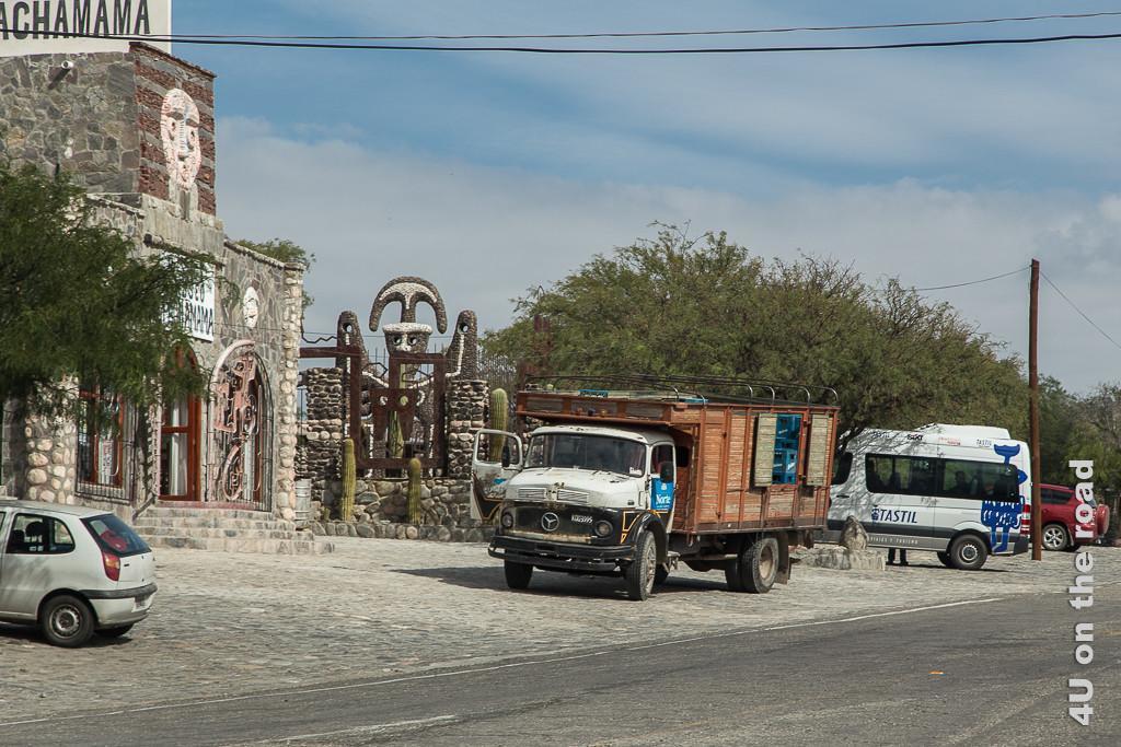 Bild Der alte Mercedes vor dem Pachamama, heisst Muter Erde, Museum gefällt uns. Es ist ein mittelgrosser Lastwagen, wohl aus den Sechzigern, mit Metallrahmenaufbau. Darin sind Getränkekisten gestapelt. Die Gebäudefront des pachamama Museums zeigt südamerikanisch-indianische Ornamentik.