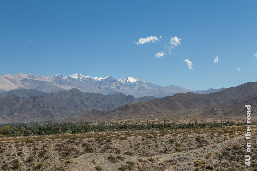 Bild Die Berge hinter Cachi. Die karge Ebene im Vodergrund, dann mehrere gestaffelte Bergketten, die hinterste höher und mit Schneemütze.