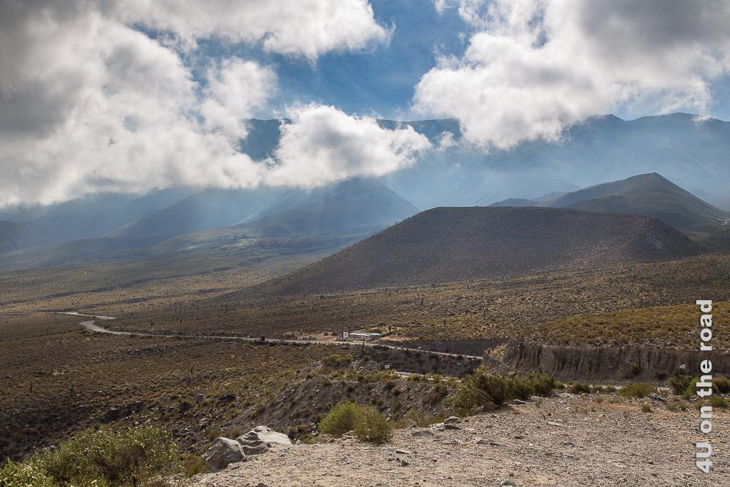 Bild Die Strasse durch die Berge im Licht aus Sonne und Wolken. Die Hänge sind snaft aber karg bewachsen. Teils unter den Berggipfeln hängen Wolken und Wolkenfetzen, zwischen denen sich in erkennbar abgesetzten Bahnen das Sonnenlicht einen Weg zum Boden bahnt.