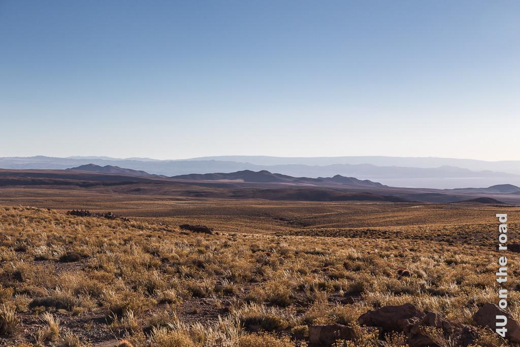 Bild Lichtstimmung am späten Nachmittag. Endlose grasbewachsene Weite, Hügel und Salzsee im Dunst im Hintergrund.