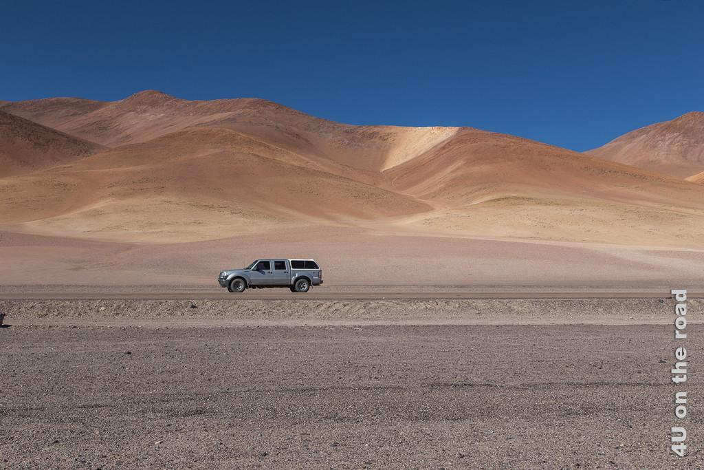 Bild Entlang des Weges nach San Pedro de Atacama - unser Mietwagen, zeigt den alten Ford Ranger vor schöner Kulisse orangfarbener Hügel