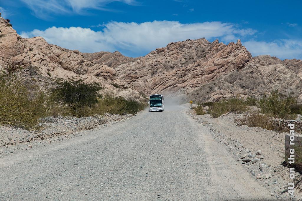Bild Gegenverkehr im Valle Calchaquies. Ein grosser Reisebus kommt uns auf der Schotterpiste zwischen den rotbraunen Felsen entgegen. Zum Glück ist die Piste hier breit genug für 2 Spuren.