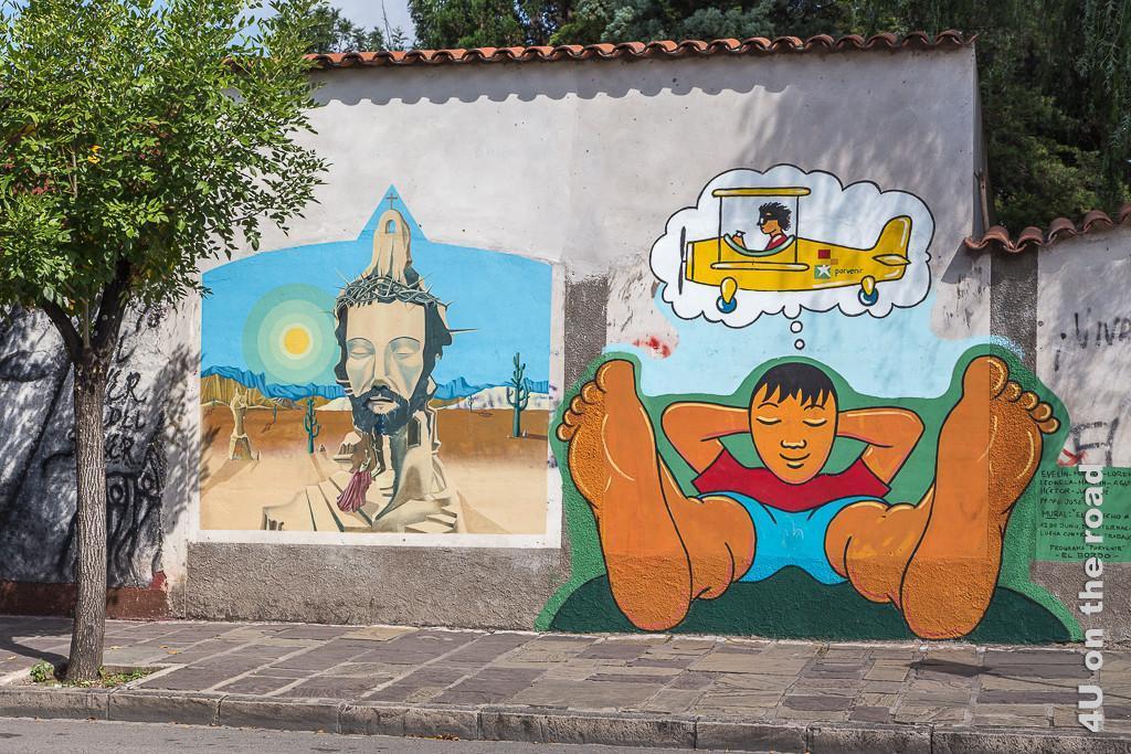 Bild Salta - Grafiti auf Mauer, Bild 1 zeigt eine angedeutete Kirche in der typischen Landschaft mit Bergen und Kakteen und einem Jesus Kopf mit Dornenkrone in der Mitte der Kirche. Bild 2 zeigt einen Jungen, der auf dem Fussweg zu liegen scheint, der von einem Propellerflugzeug träumt