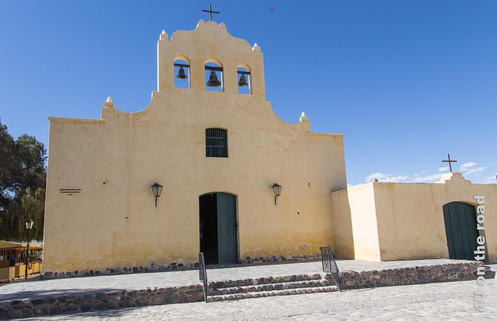 Bild Frontansicht der Iglesia San Jose in Cachi. Die Fassade des gerade mal zweigeschossigen Gebäudes ist fast fensterlos, war mal weiss getüncht, jetzt eher gelblich. Über der Mitte erhebt sich die Fassade als solche weiter und trägt die Glocken. Der Vorplatz ist sonnenbeschienen.