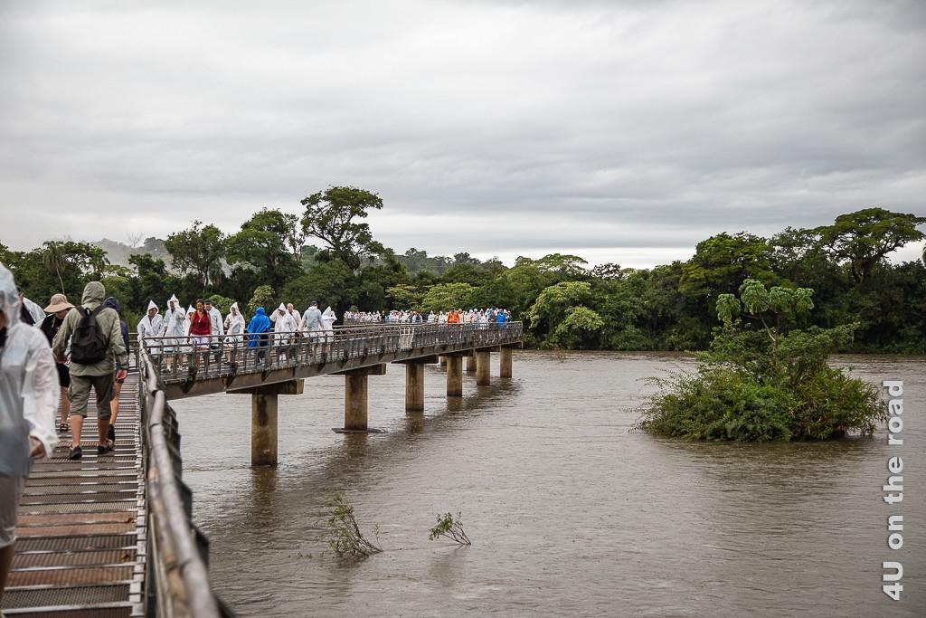 Bild Iguazu - Ku-Klux-Clan Look durch Regenpelerinen; Auf einem der Stege über den Oberlauf an den Wasserfällen geht eine Gruppe Touristen mit spitzmützigen, weissen Regenpelerinen, die sie aussehen lassen wie Mitglieder des Ku-Klux-Klan