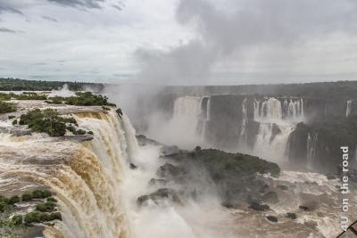 Bild Iguazu, Brasilianische Seite - Teufelsschlucht seitlich von oben; in vielen unterschiedlich breiten Kaskaden stürzen gigantische Wassermassen zwischen Urwaldbäumen, oft auch über Zwischenstufen in die lange Schlucht