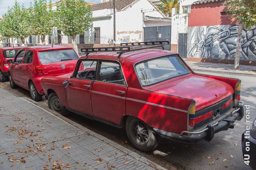 Bild Oldtimer sind alltäglich im Strassenbild von Salta, hier ein uraltes rotes Auto hinter einem modernen roten VW