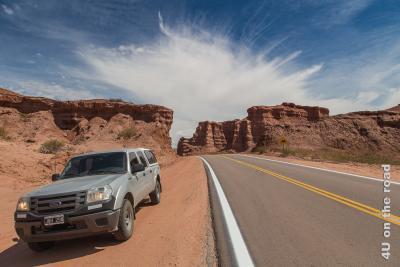 Bild Quebrada de la Conchas - Die Wolke verleiht dem Bild das gewisse Etwas. Über der Strasse durch die roten Felsen scheint am blauen Himmel eine Wolke regelrecht zu explodieren und feine, geradlinige, weisse Strahlen in alle Richtungen am Himmel auszustrecken.
