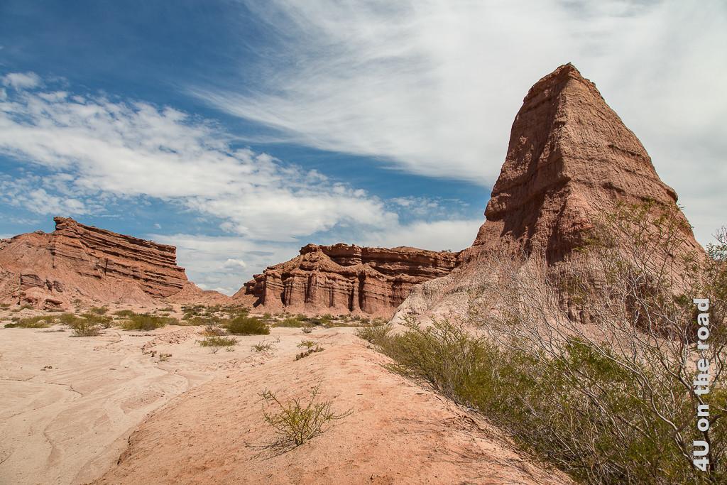 Bild Quebrada de la Conchas - Vielfältige Felsen. Immer noch sind sie rotbraun. Zwischen Monument-Valley-artigen Felsen steht einer, der aussieht wie eine sehr steile Pyramide.