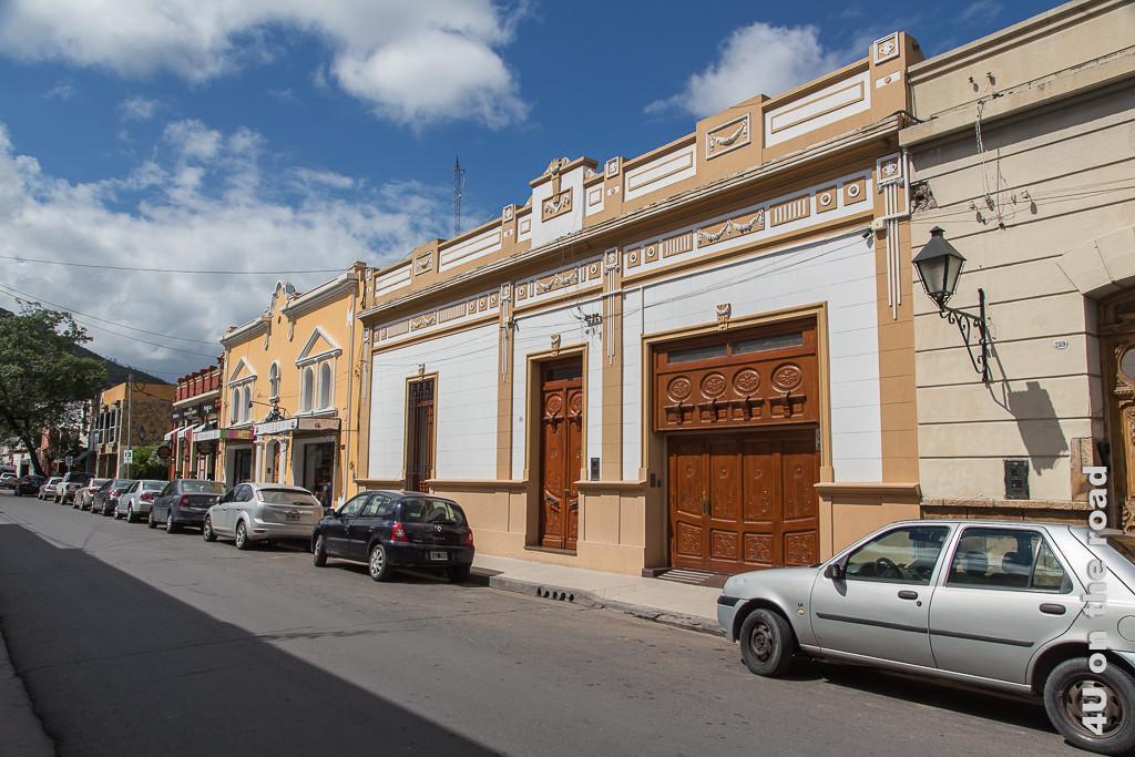 Bild Salta - Auf dem Weg zur Seilbahn. Strassenzug mit flachen, schönen, stuckverzierten Häusern in weiss und beige Tönen. Zum Teil verfügen sie über markante Holztüren und Tore.