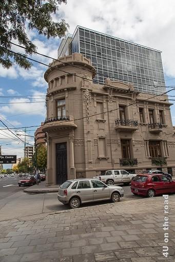 Bild Salta - alt und modern direkt nebeneinander. Im Bild altes Haus aus der Kolonialzeit und Hochhaus aus dem 70ern mit Glasfassade.