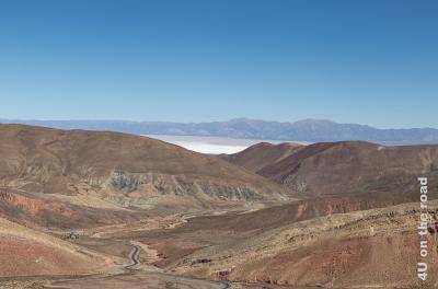 Bild Salinas Grande in der Ferne, im Vordergrund die Strasse, welche sich durch die rötlichen Felsen schlängelt