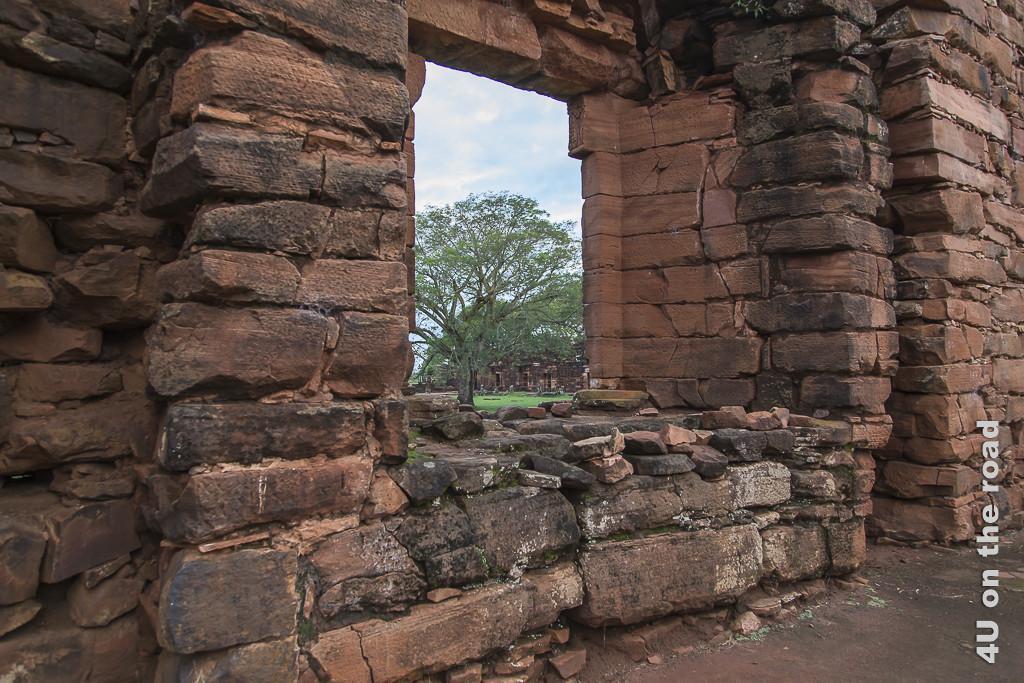 Bild Mission San Ignacio - Fenster in der Ruine - Provinz Misiones. Ein grosser gemauerter Fensterrahmen in der rötlichen Steinwand. Über die Tiefe des Fensterbereichs erschliessst sich, wie dick diese Mauern waren, circa 1 Meter.
