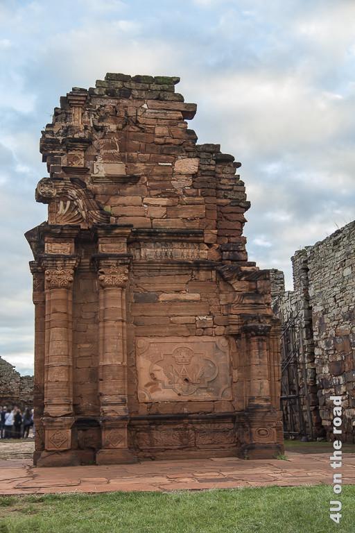 Bild Mission San Ignacio Ruine - Provinz Misiones. Ein etwa 5 Meter hoher Mauerrest aus rötlichen Steinen, an dessen Front hohe, eingearbeitete Säulen eine flache Steinplatte mit reliefartigen Symbolen und Inschrift umrahmen.