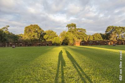 Bild Mission San Ignacio - Sonnenuntergang - Provinz Misiones. Der grasbewachsene weite Innenbereich der Mission, auf dem Gras der langgezogene Schattenwurf von Susan und Jörg in der Abendsonne. Im Hintergrund die Mauern von Wohngebäuden der Mission vor dem umgebenden Wald.