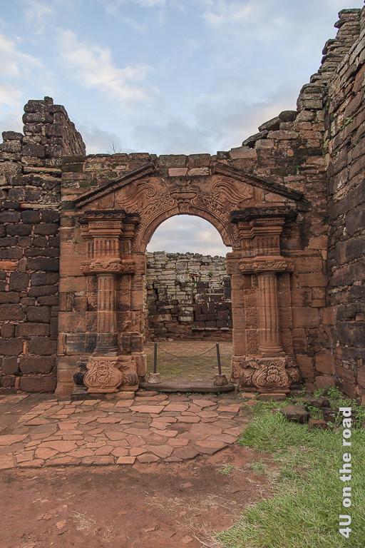 Mission San Ignacio Mini - aufwändiges Tor - Provinz Misiones. Mauer aus rötlichen Steinen mit einem Tordurchgang. Dieser ist von integrierten Säulen eingerahmt, und von einer angedeuteten Dachschräge mit Reliefbildern gekrönt, ähnlich alten griechischen Tempeln.
