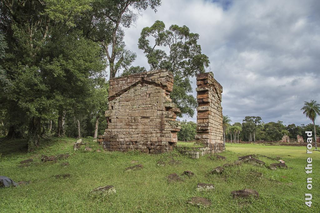 Bild Mission Santa Ana - Ruine - Provinz Misiones. Giebelmauern eines ehemaligen Wohngebäudes der Mission stehen in einer grünen Wiese, im Hintergrund Wald. In den Mauern sind die Vertiefungen zu sehen, in die das Dachende eingepasst und abgestützt wurde.
