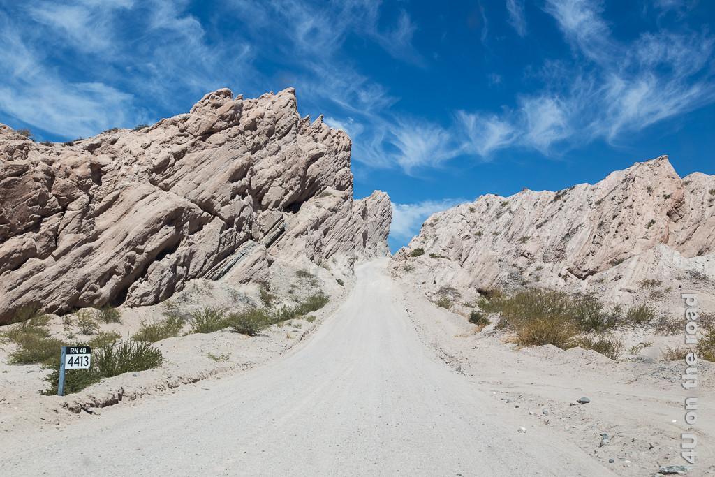 Bild Scheinbar führt die Schotterstrasse direkt in den Himmel. Valle Calchaquies, zeigt die Strasse in Mitten wilder Felsformationen mit schräg aufwärts gerichteten Schichtlinien darin.