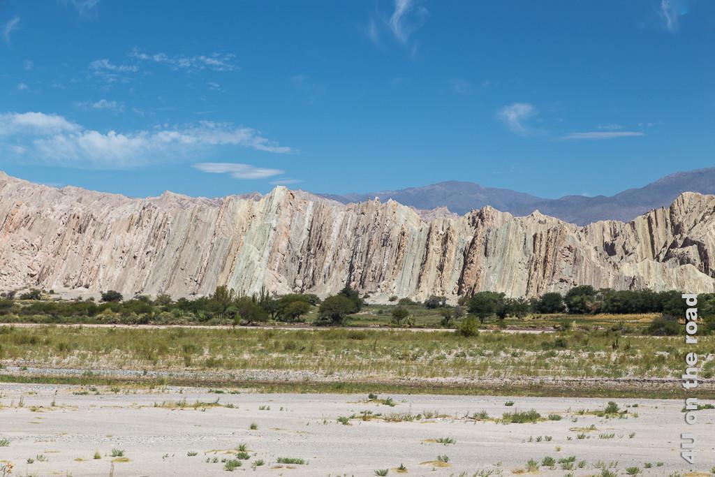 Bild Schon wieder ändern die Felsen ihr Aussehen und ihre Struktur (Valle Calchaquies). Jetzt sind sie rot-weiss gestreift enlang der nun fast senkrecht gestellten Schichtlinien in den Felsen.