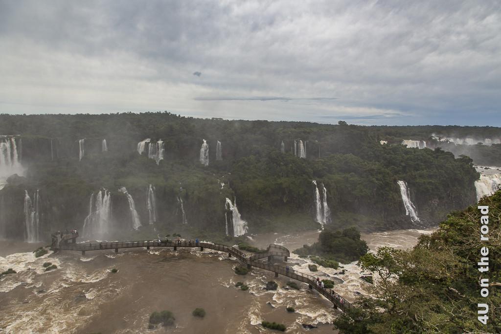 Bild Iguazu, Brasilianische Seite von oben - Steg ins Wasser über eine unteren Terrasse der Wasserfälle im breiteren Teil des Tals. Der Steg ist leicht Gischtumweht.